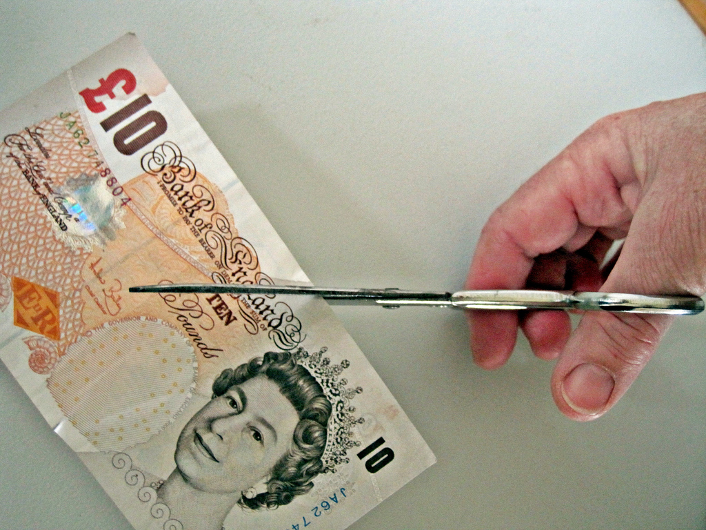 Scissors cutting money in half